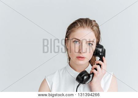 Young woman talking on retro tube isolated on a white background