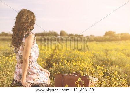 Woman Sitting In A Field Looking Far Away
