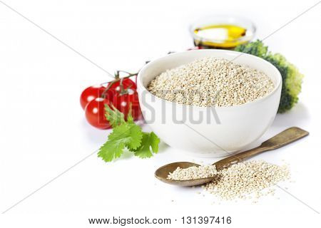 Bowl of healthy white quinoa seeds with vegetables over white