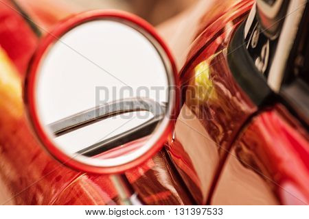Rear-view mirror on red veteran car. Vintage car. Old automobile. Vibrant colors.