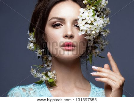 Beautiful brunette girl in blue dress with a gentle romantic make-up pink lips and flowers. The beauty of the face. Portrait shot in the studio. poster