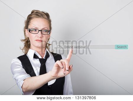 online webinar written in search bar on virtual screen. technology, internet and networking concept. Internet technologies in business and home. woman in business suit and tie, presses a finger on a virtual scree.