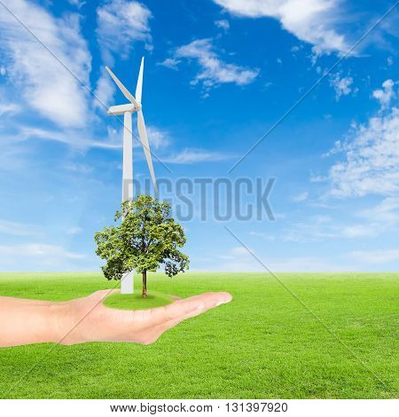 Green Earth concepthand holding tree with wind turbine against green field and blue sky
