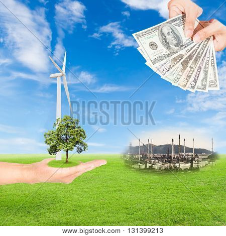 Carbon credits concepthand holding tree and wind turbine and US Dollars banknote with oil refinery plant against green field and blue sky background