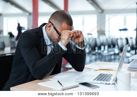 Overworked, depressed and exhausted businessman at his desk with a pile of work