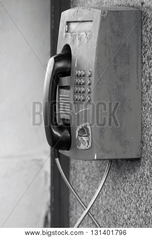 the big old payphone of monochrome color a closeup and located outdoor on a wall