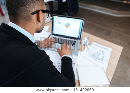 Back view of businessman typing on laptop in the office