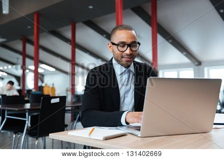 Handsome businessman working and using laptop in the office