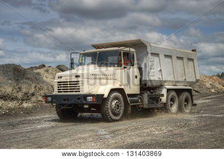 Poltava Region Ukraine - June 26 2010: Dump truck driving along the opencast road with mud