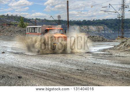 Poltava Region Ukraine - June 26 2010: Mining crew bus driving along the opencast road with mud splashes
