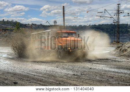Poltava Region Ukraine - June 26 2010: Mining crew bus making mud splashes driving at high speed along the opencast