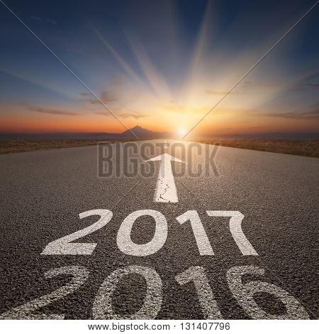 Driving on an empty road towards the setting sun and sunbeams to upcoming new 2017 year and leaving 2016 behind. Concept for success and passing time.