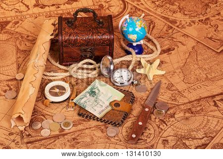 Accessories for the traveler: a compass, a pocket watch, a globe, a treasure trove of coins and a knife on a background of antique maps.