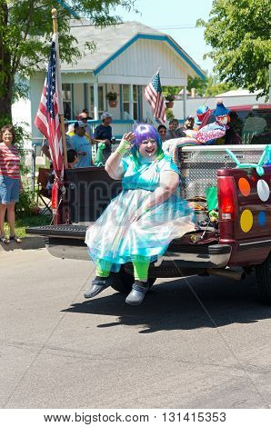 WEST ST. PAUL, MINNESOTA - MAY 21, 2016: Clown in costume waves to crowd from bed of pickup truck during annual West St. Paul Days Grande Parade in West St. Paul on May 21, 2016.