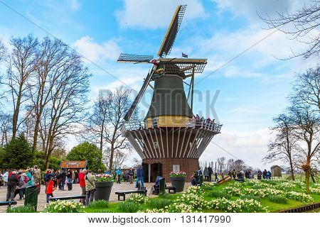 Lisse, Netherlands - April 4, 2016: Windmill and flowerbeds in the spring garden Keukenhof, tourists around