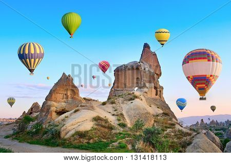Hot air balloons flying over spectacular landscape of fairy chimneys carved in volcanic tuff by erosion. Cappadocia Turkey