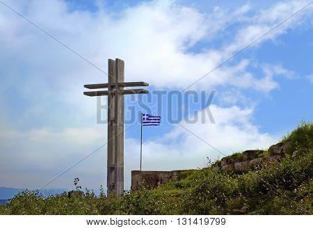 the big wooden cross at Piraiki Piraeus Greece and the greek flag
