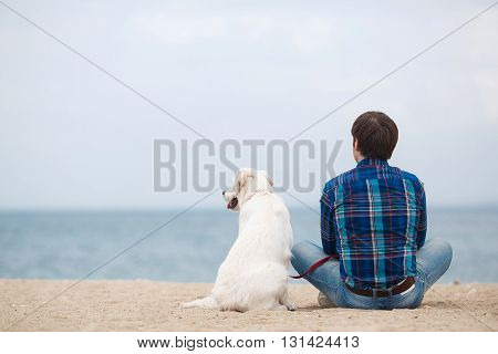 Guy,brunette with beautiful hair,wearing a blue plaid shirt and blue jeans,sitting on a sandy beach in the spring with his faithful friend,a dog breed Golden Retriever,his back turned to the photographer,face to the blue ocean