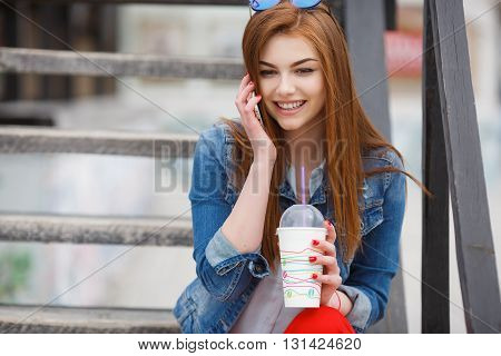 Cute young woman with long red hair,light makeup and red nail Polish,dressed in a blue denim jacket,sitting on the wooden stairs in the fresh summer air, talking on the mobile phone,cute smiling and drinking a cocktai