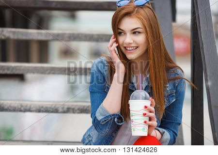 Cute young woman with long red hair,light makeup and red nail Polish,dressed in a blue denim jacket,sitting on the wooden stairs in the fresh summer air, talking on the mobile phone,cute smiling and drinking a cocktail