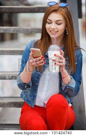 Beautiful girl model looks,long red hair,light makeup and red nail Polish,dressed in a blue denim jacket,sitting on the wooden stairs in the fresh summer air, reading a text message on your mobile phone and drinking a cocktail