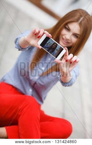 The red-haired girl with model looks,light makeup and red nail Polish,dressed in a light plaid shirt,taking a selfie on your mobile phone,sitting on the wooden deck in the fresh air in the summer