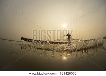 Asian Fisherman action on the boat fishingnet.