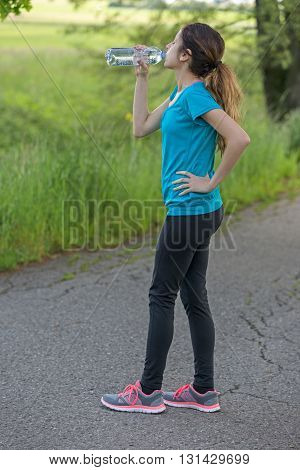 Sporty woman drinking water outdoors in nature.