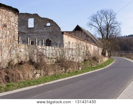 Road beside a medieval wall and a ruinous building in Siedlecin, Silesia, Poland