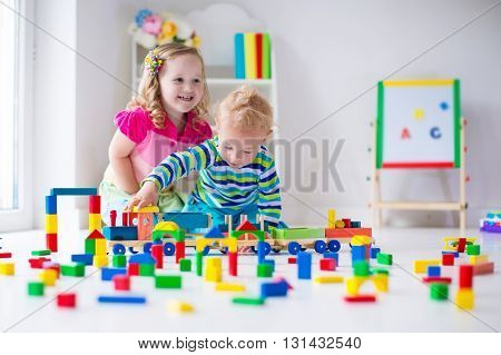 Kids play at day care. Two toddler children build tower of colorful wooden blocks. Child playing with toy train. Educational toys for preschool and kindergarten.