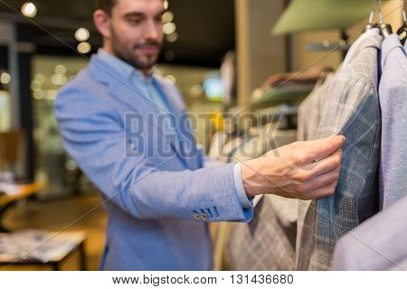 sale, shopping, fashion, style and people concept -close up of happy young man in suit choosing clothes in mall or clothing store