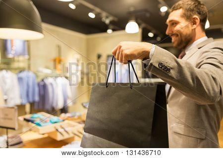 sale, fashion, retail, business style and people concept - close up of happy man in suit with shopping bags at clothing store