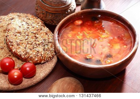 Nice wooden bowl with vegetable soup near bread and tomatoes