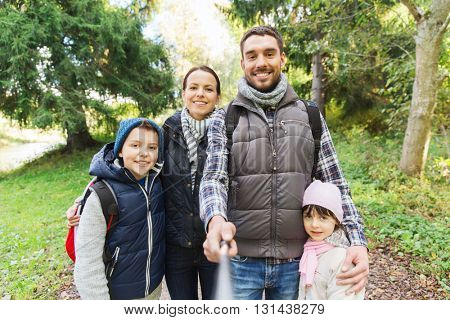 technology, travel, tourism, hike and people concept - happy family with backpacks taking picture by selfie stick and hiking
