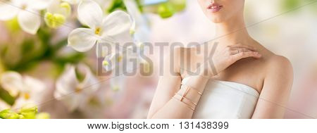 glamour, beauty, jewelry and luxury concept - close up of beautiful woman with golden ring and bracelet over natural spring lilac blossom background