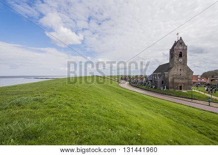 Wierum The Netherlands - April 18 2016: Church of Wierum with Waddensea dike in Friesland in the Netherlands.