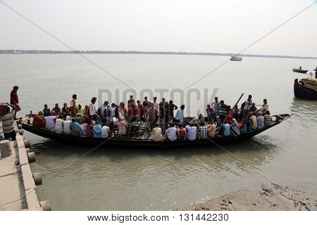 GOSABA, INDIA - FEBRUARY 13: wooden boat crosses the Ganges River on February 13, 2014 in Gosaba, West Bengal, India. To use a small wooden is easy, fast and cheap way how to cross the Ganges River.