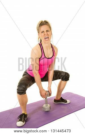 A woman doing a squat with a weight trying her best to stand back up.