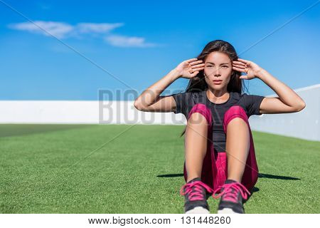 Sit-ups fitness woman doing situps training core abs exercises outside. Fit female sport model girl working out outdoors on grass. Mixed race Asian Caucasian athlete doing crunches.