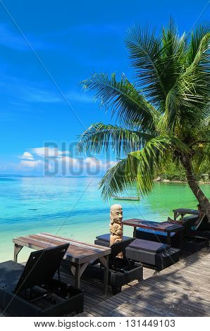 Tropical beach in Thailand with palm tree, sand and totem pole
