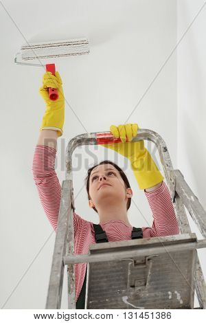 Young Worker Paint Ceiling In A Room