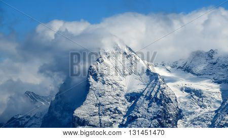 Snowy mountains with clouds over the peak and mist