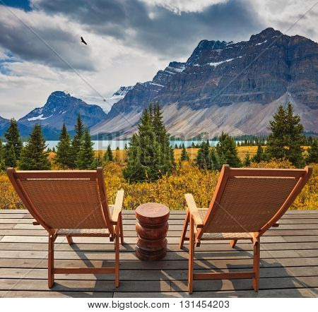 On the wooden platform there are two deckchairs beside a beautiful lake. Cold autumn day in the Rocky Mountains of Canada