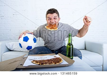 young man watching football game on television celebrating goal crazy happy jumping on sofa couch at home with ball beer bottle and pizza in his mouth looking excited and cheerfull