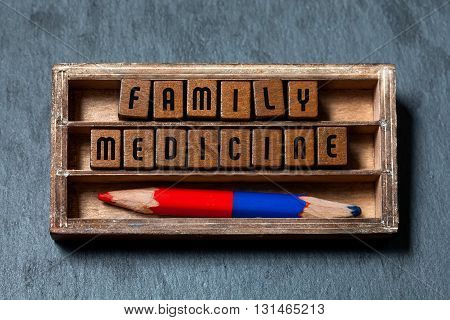 Family medicine conceptual image. Vintage blocks with retro style letters, colored pencil, aged wooden box. Gray stone background, macro view, soft focus
