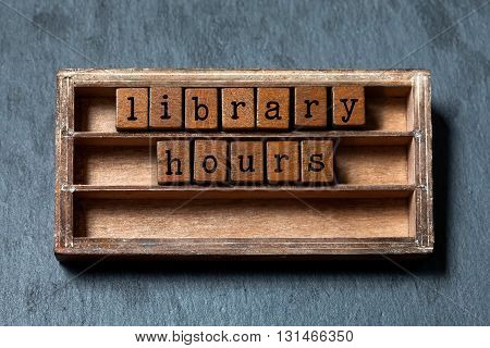 Library hours conept. Vintage blocks with letters, aged wooden box. Gray stone background, macro