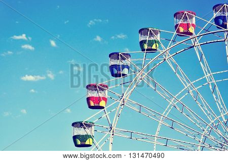 Colorful Ferris wheel at amusement park against blue sky