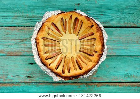 Homemade round syrnik quark pie with apples baked in foil on turquoise wooden table overhead view