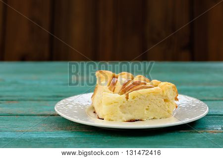 Piece of syrnik light quark pie with apples on old wooden table painted turquoise copyspace