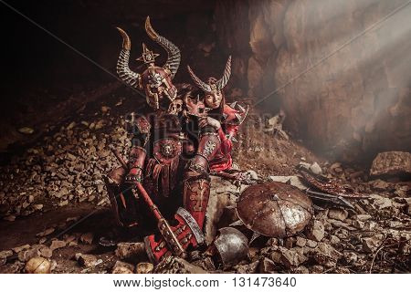 Couple Of Knights In Armor With Axe. Catacombs On The Background.